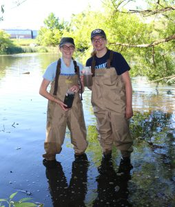 Two Etown students stand in Lake Placida, holding samples they collected.