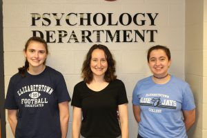 Two Etown students and their prfessor smiling at camera in front of Psychology department sign.