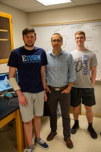 Two Etown students with professor, smiling at camera in Esbenshade lab.